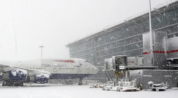 A British Airways plane is seen on the tarmac at Heathrow Airport, after all flights at the airport were grounded because of snow