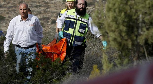 Israeli rescue workers carry the body of tourist Christine Logan after she was found in a wooded area outside Jerusalem (AP)