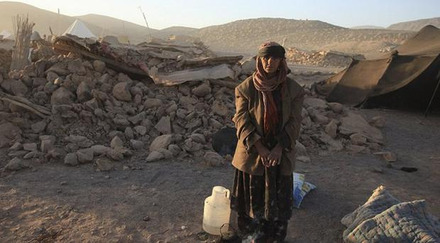 A woman warms herself outside her destroyed home in southeastern Iran (Fars News Agency, Hamid Sadeghi)