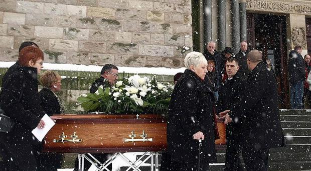 The sisters of 'Disappeared' victim Peter Wilson walk alongside his coffin at his funeral in north Belfast