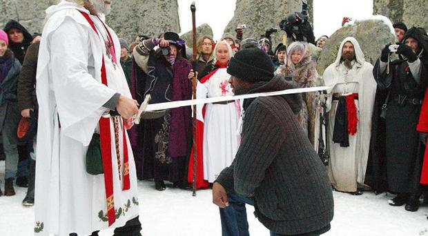 Arthur Pendragon 'knights' soldier Lance Corporal Paul Thomas during the winter solstice at Stonehenge