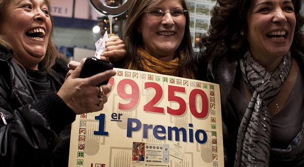 Employees of a lottery office that sold the winning number celebrate (AP)