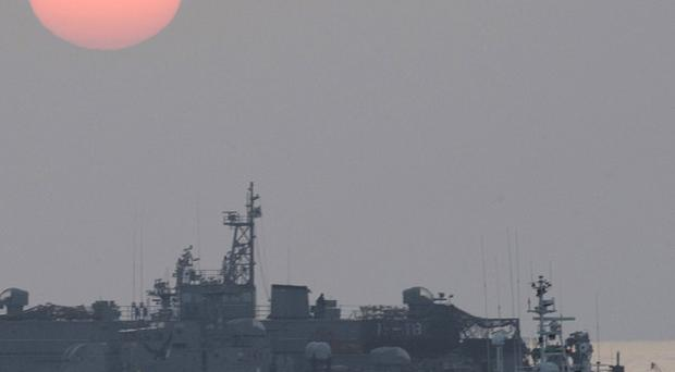 A government ship sails past the South Korean navy's floating base as the sun rises near Yeonpyeong island, South Korea (AP)