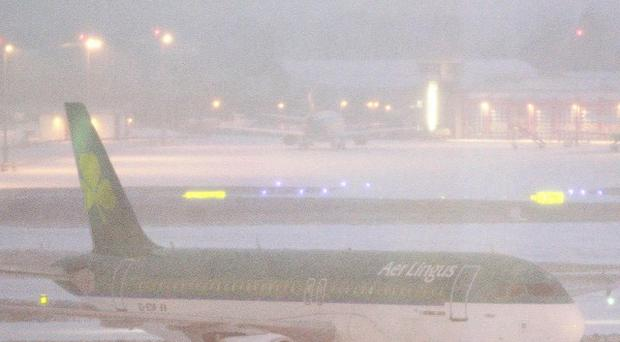 An Aer Lingus aircraft taxis through the snow on the runway at Dublin airport.