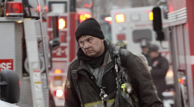 A firefighter walks away from the scene of a fire in Chicago where officials say a wall collapsed killing two men. (AP)