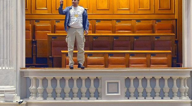 Adrian Sobaru gestures before throwing himself from a balcony in Romania's Parliament