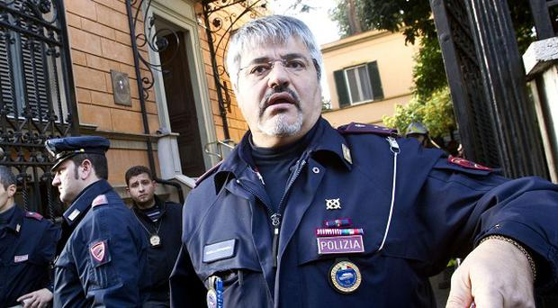 Police officers outside the Chilean embassy in Rome after a parcel bomb exploded (AP)