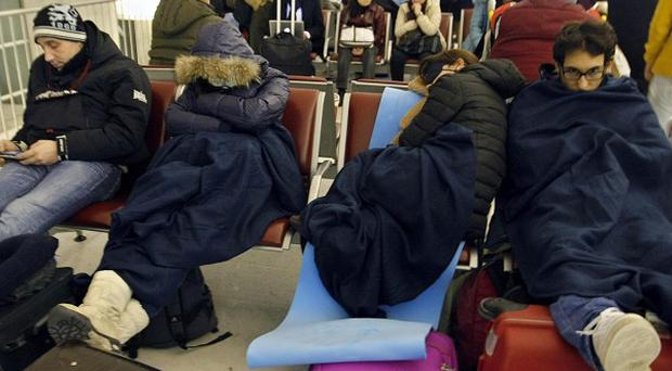 Passengers wait for their flights in a terminal after sleeping at Charles de Gaulle Roissy airport, near Paris(AP)