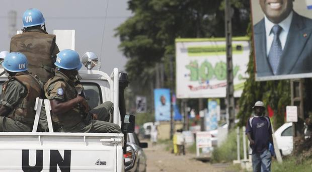 UN forces drive past a billboard for President Laurent Gbagbo in Ivory Coast (AP)