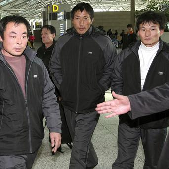 Three Chinese fishermen wait for their flight after being released at Incheon International Airport west of Seoul (AP)