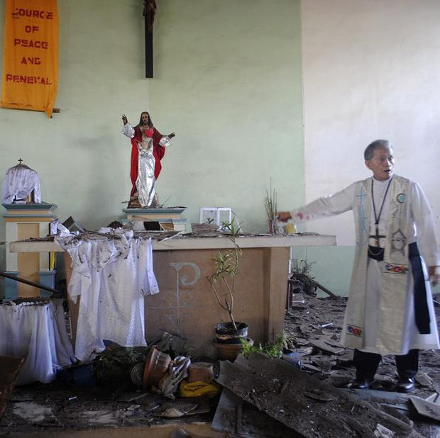 Fr Romeo Villanueva surveys the damage to a Catholic chapel following an attack on the volatile island of Jolo (AP)