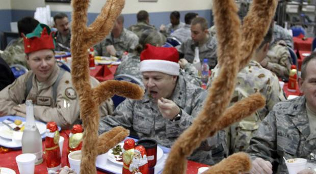 Soldiers with the Nato-led International Security Assistance Force enjoy Christmas lunch in Kabul, Afghanistan (AP)