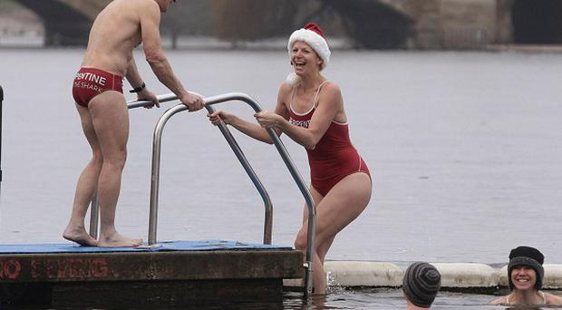 Members of the Serpentine Swimming Club take part in their annual Christmas Day swim in the Serpentine Lido, in Hyde Park
