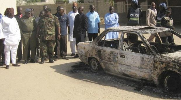 Bystanders gather around a burned car outside the Victory Baptist Church in Maiduguri, Nigeria, after an attack on Christmas Eve