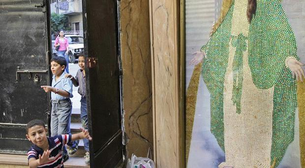 Children run past a painting of the Virgin Mary inside the entrance of the Virgin Mary Coptic church in the el-Asafra area of Alexandria (AP)