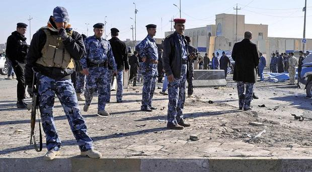 Security forces inspect the scene of two suicide bomb attacks in Ramadi, Iraq (AP)