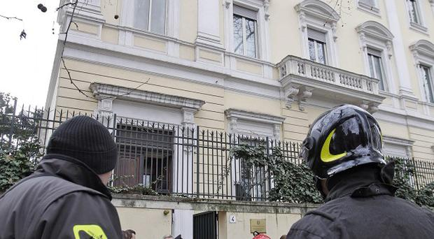 Firefighters stand outside the Greek Embassy in Rome after a package bomb was found (AP)