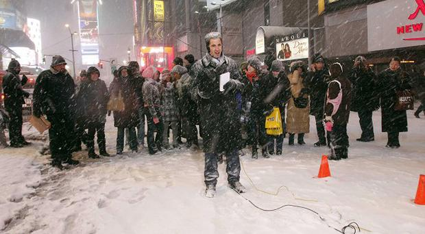 WCBS newsman Michael Herzenberg prepares to give a live report during a snowstorm in New York's Times Square (AP)