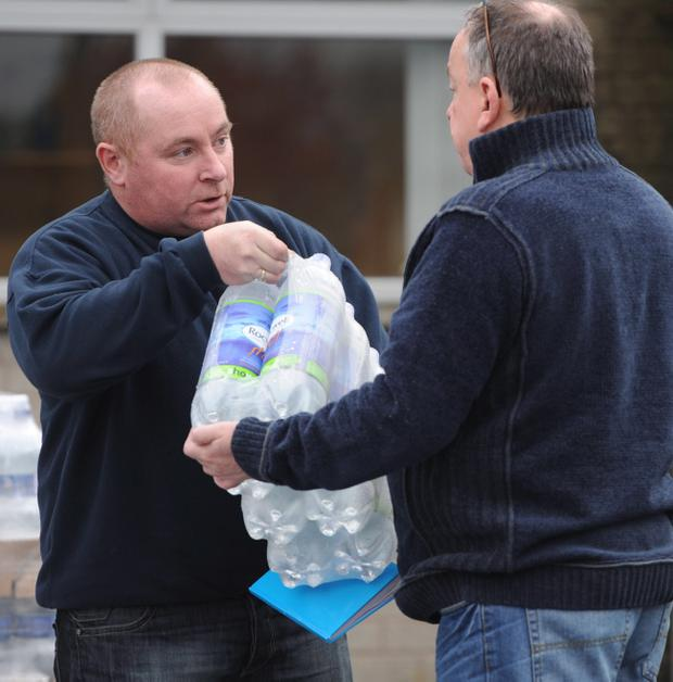 Tempers flare as families queue for the last few crates of bottled water at NI Water in Ballymena