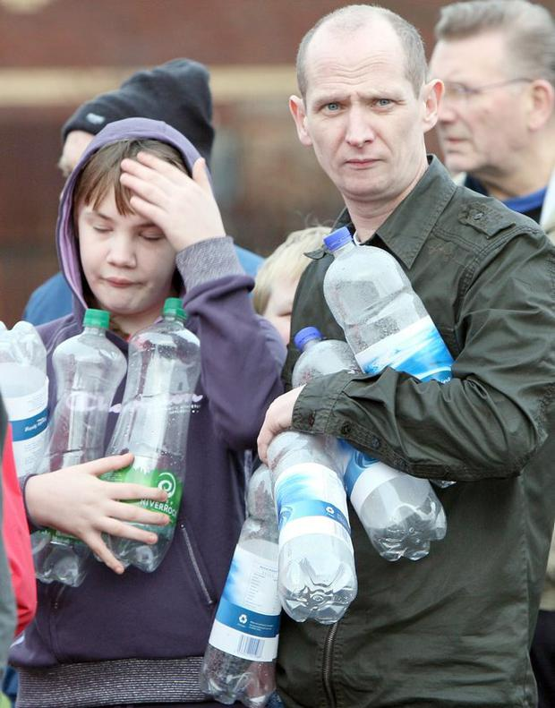 People wait in line at Avoniel leisure centre in east Belfast with empty bottles to get drinking water December 29, 2010.