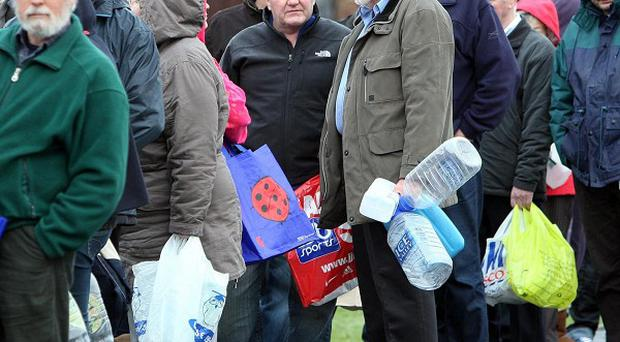 People wait in line at Avoniel leisure centre in east Belfast with empty bottles to get drinking water