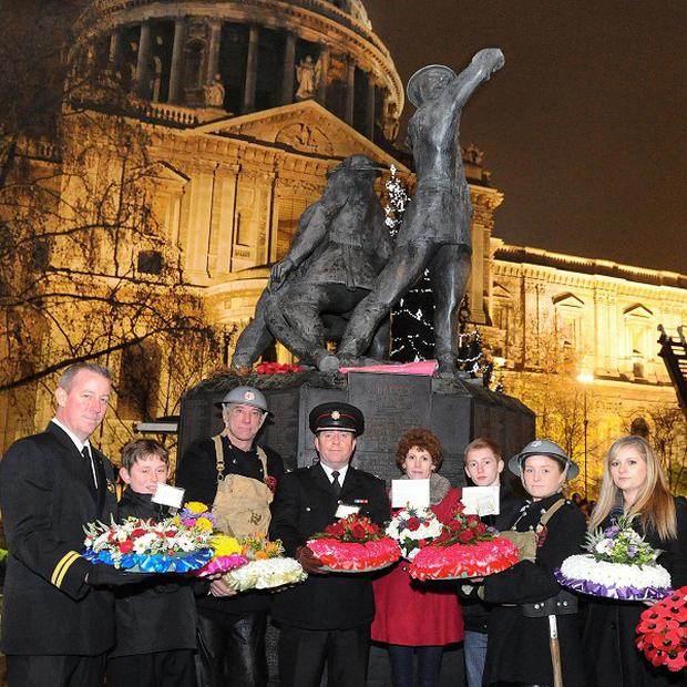 Wreath-bearers stand at a memorial outside St Paul's Cathedral to the firefighters who died during the Second World War