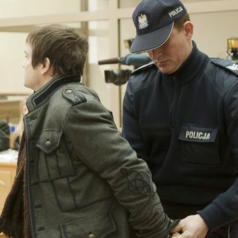 A police officer leads Anders Hogstrom into the court in Krakow, Poland (AP)