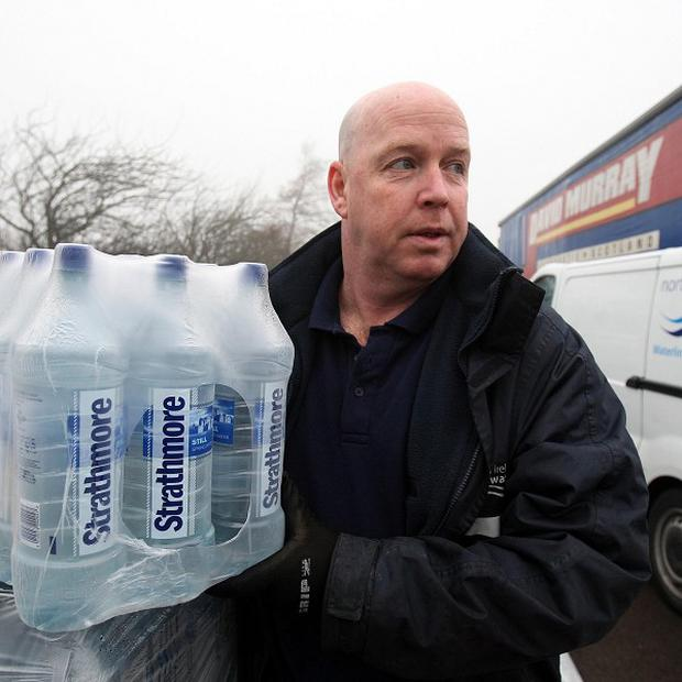 A Northern Ireland Water employee with bottled water supplied by the Scottish government in Belfast