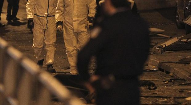 Police forensic experts gather evidence at the scene following a bomb explosion outside a closed night club in Athens (AP)