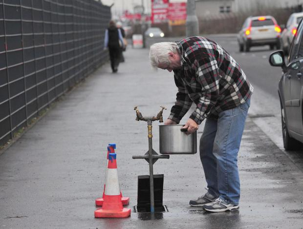 A man fills up a pot from a water tap at Olympia Lesiure Centre, Belfast