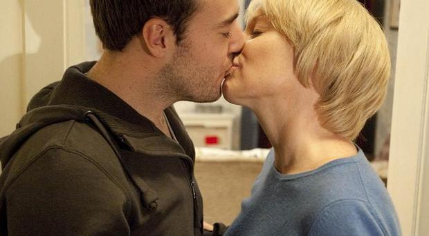 Sally Webster, played by Sally Dynevor, kisses Tyrone Dobbs, played by Alan Halsall