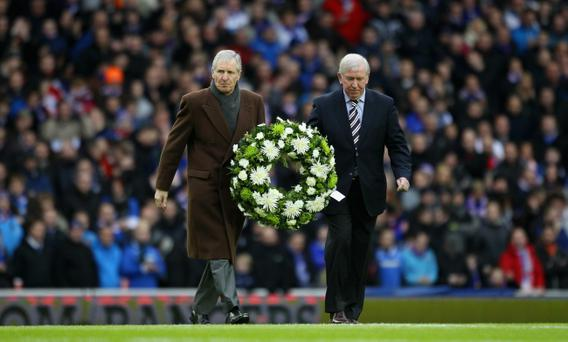 GLASGOW, SCOTLAND - JANUARY 02: John Greig former Rangers captain and Billy McNeill former Celtic captain hold a wreath prior to the Clydesdale Bank Premier League match on January 2, 2011 in Glasgow, Scotland. Scotland. Rangers and Celtic fans observed a one minutes silence to mark the 40th anniversary of the Ibrox disaster, when sixty six football supporters lost their lives at the end of the 1971 New Year match. (Photo by Jeff J Mitchell/Getty Images)
