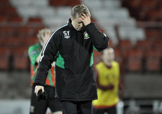 Glentoran manager Scott Young troops off dejectedly after watching his side beaten by Portadown on Saturday