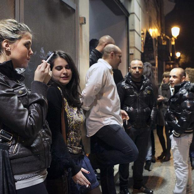 People smoke outside a nightclub in Madrid early on Sunday after Spain's new anti-smoking law came into effect (AP)