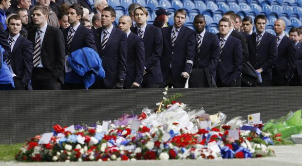 GLASGOW, UNITED KINGDOM - JANUARY 3: Rangers players walk past floral tributes ahead of a memorial service to commemorate the 40th Anniversary Memorial of the Ibrox Disaster held at the Ibrox stadium on January 3, 2011 In Glasgow, United Kingdom. The Ibrox disaster occurred on January 2, 1971 at the end of an Old Firm game when 66 people lost their lives in a crush as crowds left the stands. (PHoto by Danny Lawson - pool/Getty Images)