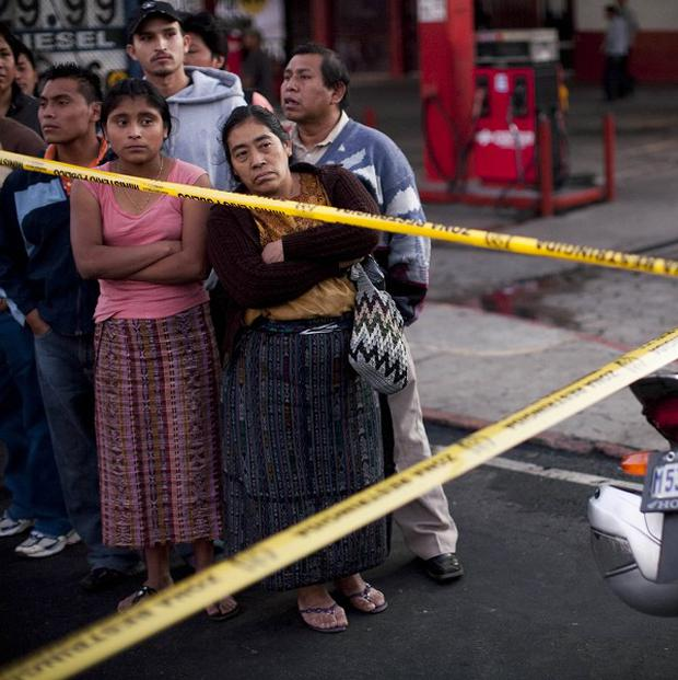 Witnesses at the scene of a fatal bus fire in Guatemala City (AP)
