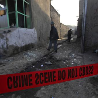 Afghan police officers look for clues near the site of an explosion in Kabul (AP)
