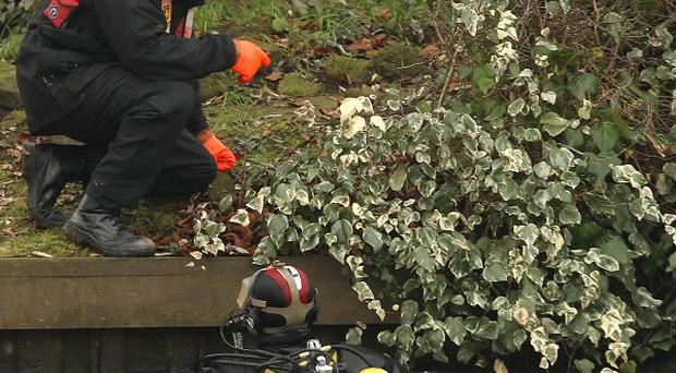 A police diver searches the river Thames in Surrey for two missing men after a boat carrying six passengers capsized