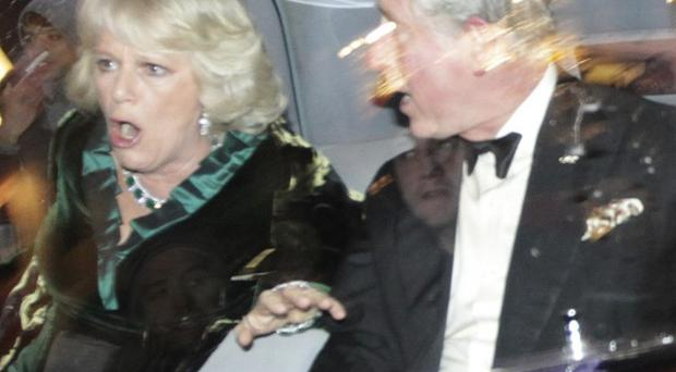 Prince Charles and the Duchess of Cornwall react as their car is attacked (AP Photo/Matt Dunham)