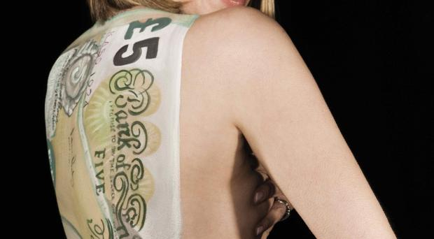 TV presenter Kate Garraway poses with the image of a five pound note printed on her back to promote the micro-lending website called lendwithcare.org.