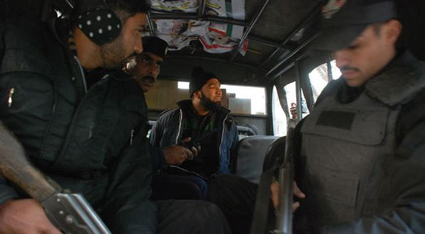 Commando of Pakistan's Elite force Mumtaz Qadri, center, who allegedly killed Punjab's governor Salman Taseer sits in a police van in Islamabad, Pakistan on Tuesday, Jan. 4, 2011. An intelligence official interrogating the suspect, identified as Mumtaz Qadri, told The Associated Press that the bearded elite force police commando was boasting about the assassination, saying he was proud to have killed a blasphemer. The governor of Pakistan's powerful Punjab province was shot dead Tuesday by one of his guards in the Pakistani capital, police said, the killing was the most high-profile assassination of a political figure in Pakistan since the slaying of former Prime Minister Benazir Bhutto in December of 2007. (AP Photo/Tariq Waseem)