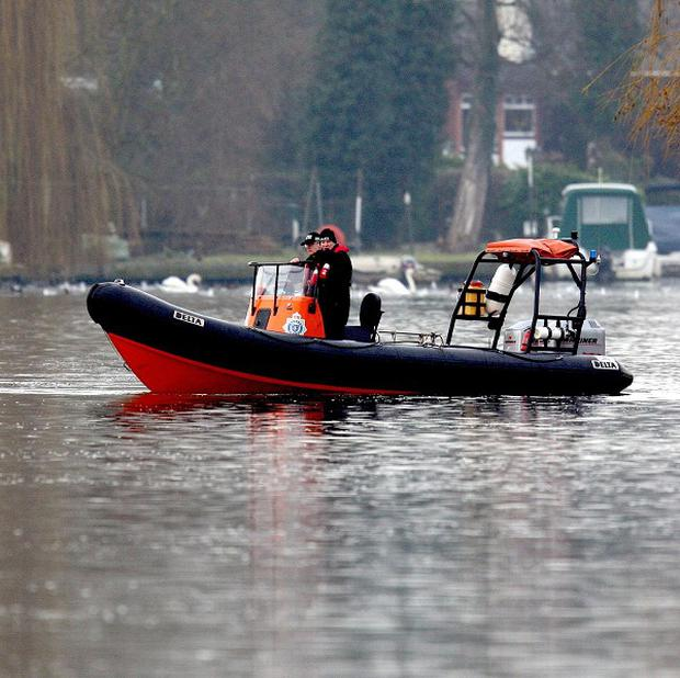 Police search the River Thames near Shepperton after a boat carrying six passengers capsized