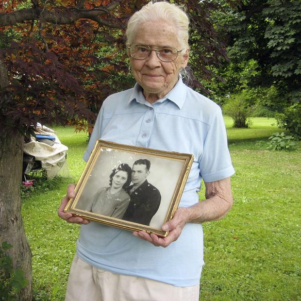 Jean Stevens holds a photograph from the 1940s of herself and her late husband, James (AP)