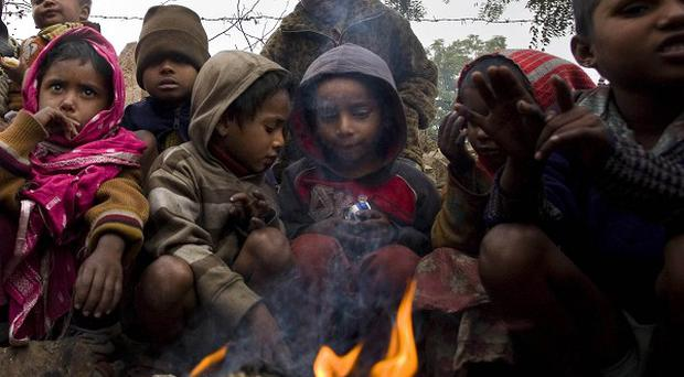 Children huddle close to a fire during a cold winter morning in Gurgaon, India (AP)