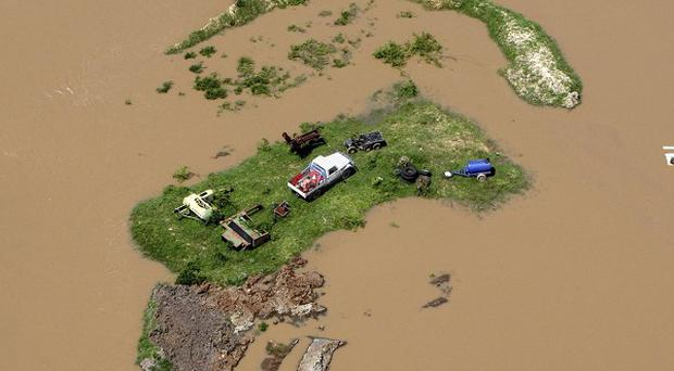 An island is formed by floodwater stranding vehicles and other equipment in Rockhampton, Australia (AP)
