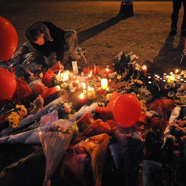 Kyle Binning lights candles at a memorial outside Millard South High School in Omaha, Nebraska, where a 17-year-old gunman killed an assistant principal (AP)