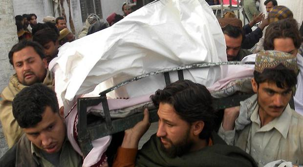The body of a Pakistani killed in a suicide attack at a bath house in Afghanistan is carried out of hospital (AP)