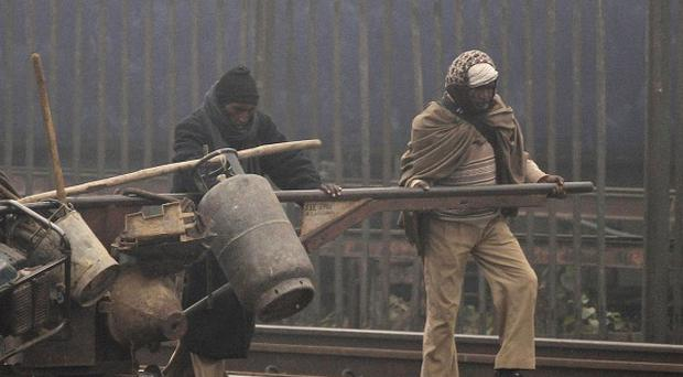 Near-freezing temperatures have killed dozens of homeless people across northern India (AP)