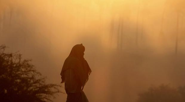 An Indian man wrapped in warm clothing walks along a street as thick fog and freezing conditions hit the city of Hyderabad (AP)