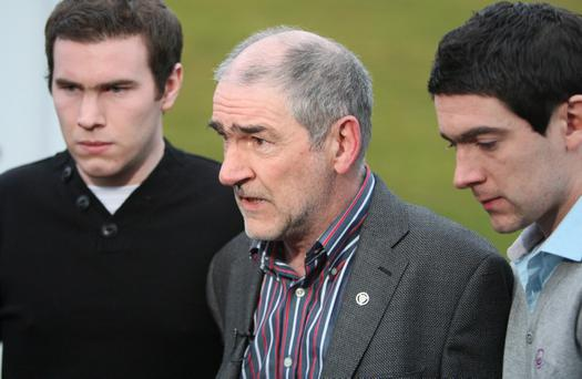 A distraught Mickey Harte, with sons Matthew (left) and Michael at their family home near Ballygawley yesterday following the death of daughter Michaela, wants Tyrone to play this weekend.